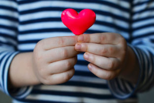 Child Holding A Small Pink Heart. Symbol Of Love Family Hope.